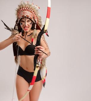 Kobieta na obrazie rdzennych ludów ameryki z łukiem i strzałą pozuje na białym tle