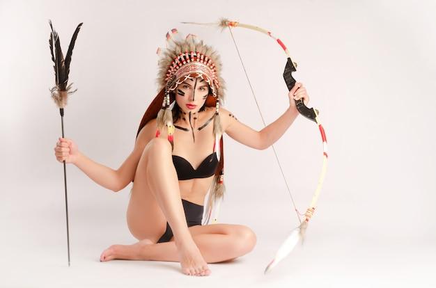 Kobieta na obrazie rdzennych ludów ameryki z łukiem i strzałą pozuje siedząca na jasnym tle
