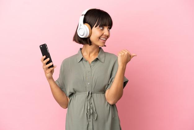 Kobieta na odosobnionym tle w ciąży i słuchająca muzyki, wskazując bok