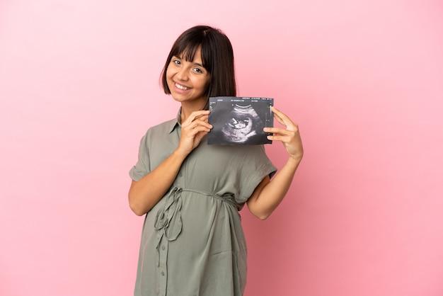 Kobieta na odosobnionym tle w ciąży i trzymająca usg
