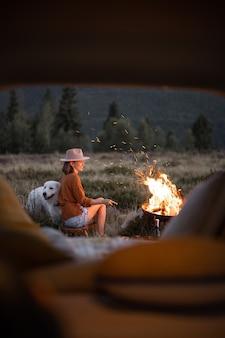 Kobieta na pikniku z ogniskiem w górach