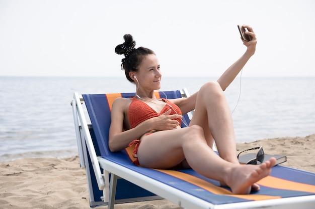 Kobieta na plażowym krześle bierze selfie