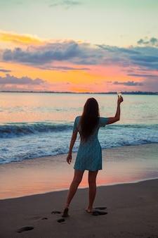 Kobieta na plaży, ciesząc się wakacjami, patrząc na morze