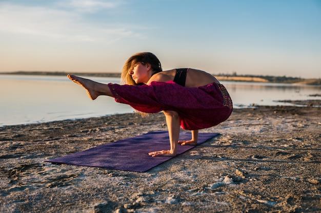 Kobieta na plaży o zachodzie słońca robi asany jogi. poranny trening rozgrzewkowy z naturalnym rozciąganiem