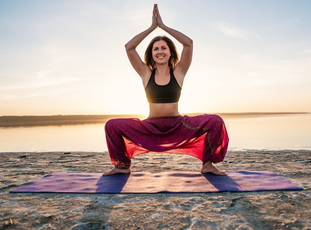 Kobieta na plaży o zachodzie słońca zaczyna robić trening asan jogi. poranny trening rozgrzewkowy z naturalnym rozciąganiem