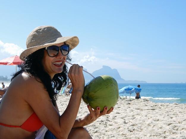 Kobieta na plaży pijąca wodę kokosową w rio de janeiro