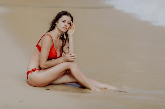 Kobieta na plaży siedzi w piasku patrząc na ocean ciesząc się słońcem i letnimi podróżami wakacje wypoczynek.