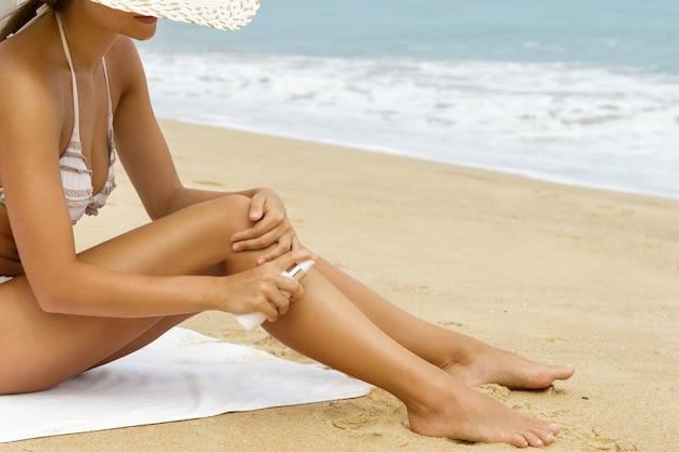 Kobieta na plaży stosując spray do oprysków na ciele