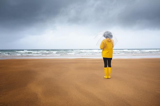 Kobieta na plaży widziana od tyłu, patrząca na morze w deszczu, z przezroczystym parasolem, ubrana w płaszcz przeciwdeszczowy i żółte buty, w pochmurny dzień z burzami. kopiuj przestrzeń