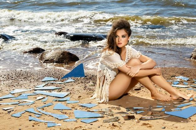 Kobieta na plaży z odłamkami lustra