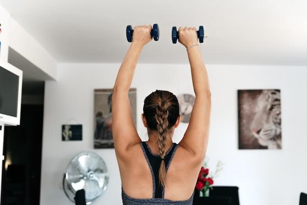 Kobieta na plecach ćwicząca z hantlami w salonie.