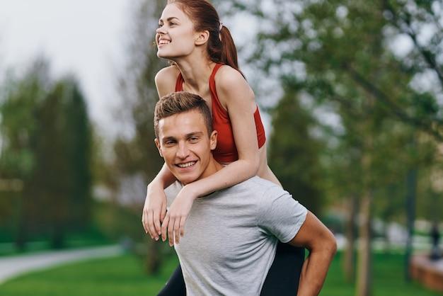 Kobieta na plecach mężczyzn na zewnątrz spacer zabawny styl życia.