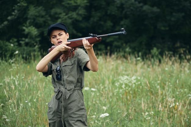 Kobieta na polowanie przyrody z pistoletem w zielonych kombinezonach zielonych liści leśnej przestrzeni