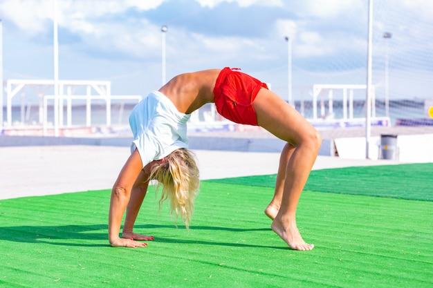 Kobieta na polu robi ćwiczenia jogi fitness. element acroyoga zapewniający siłę i równowagę