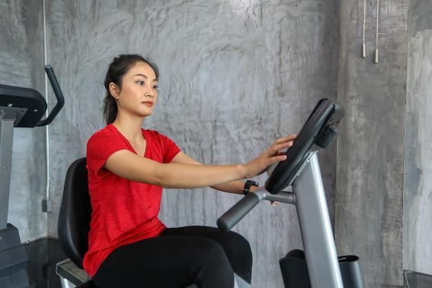 Kobieta na rowerze siłowni robi ćwiczenia cardio.