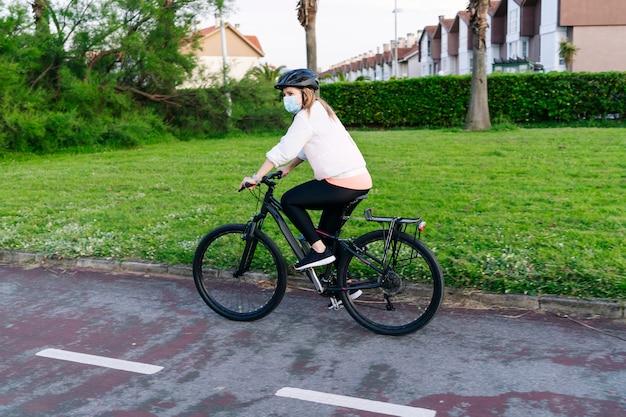 Kobieta na rowerze z maską bezpieczeństwa na twarzy