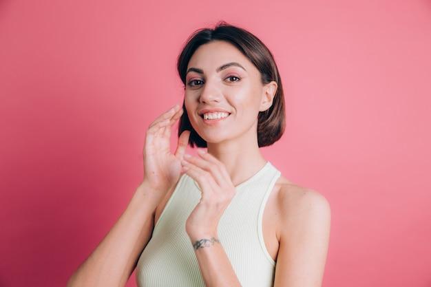 Kobieta na różowym tle szczęśliwa buźka uśmiecha się patrząc w kamerę. pozytywna osoba.