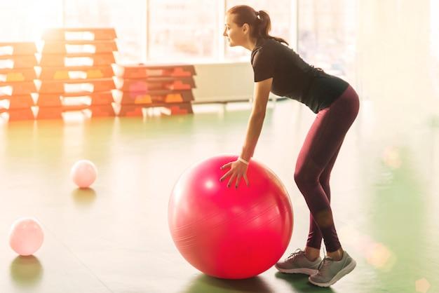 Kobieta na siłowni, ćwiczenia z piłką pilates