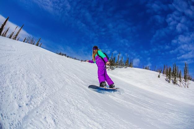 Kobieta na snowboardzie w górach sheregesh.
