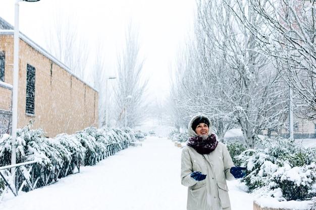 Kobieta na spacerze po mieście podczas opadów śniegu.