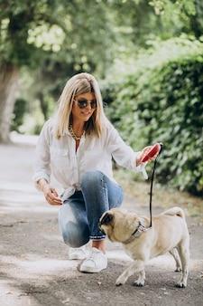 Kobieta na spacerze w parku ze swoim zwierzakiem-mopsem