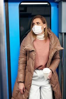 Kobieta na stacji metra nosząca na twarzy ochronną chirurgiczną maskę higieniczną zapobiega ryzyku koronawirusa