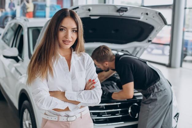 Kobieta na stacji paliw acr sprawdza swój samochód z mechanikiem