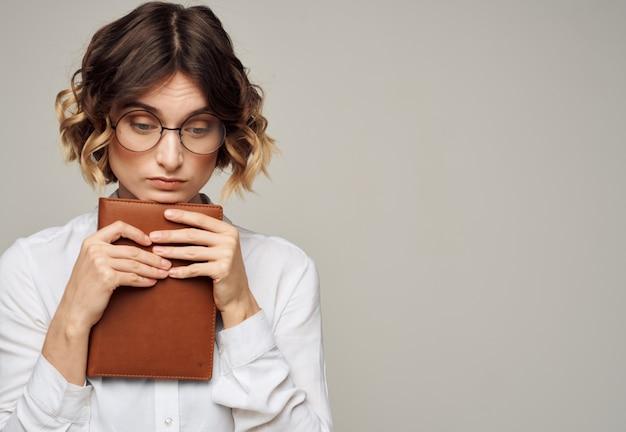 Kobieta na szarym tle z książką w dłoniach i na sobie okulary kopia przestrzeń