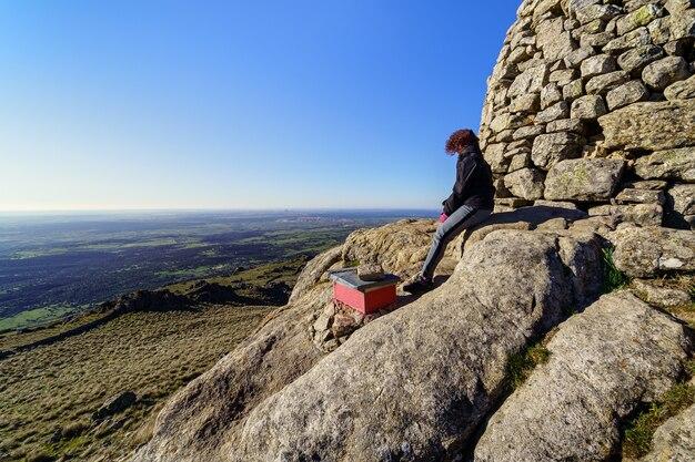 Kobieta na szczycie góry kontemplująca widoki po wejściu na szczyt. madryt.