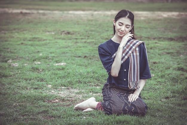 Kobieta na tajlandzkim tradycyjnym odzieżowym obsiadaniu na trawie