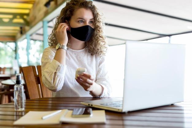 Kobieta na tarasie pracuje z maską