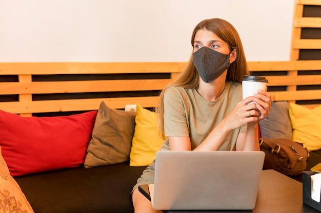 Kobieta na tarasie z laptopem w masce