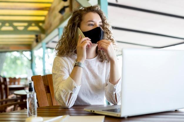 Kobieta na tarasie z maską rozmawia przez telefon