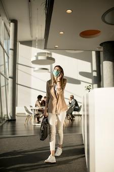 Kobieta na telefon komórkowy chodzenie w biurze i noszenie maski jako ochrona przed wirusami