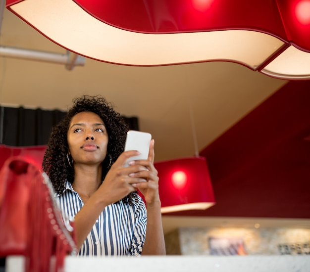 Kobieta na telefon komórkowy czeka na swój lot na lotnisku