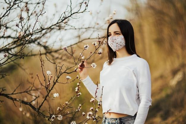 Kobieta na tle kwitnącego drzewa wiosną pokazuje na twarzy maskę medyczną.