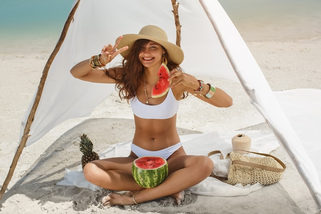 Kobieta na tropikalnej plaży, jedzenie arbuza
