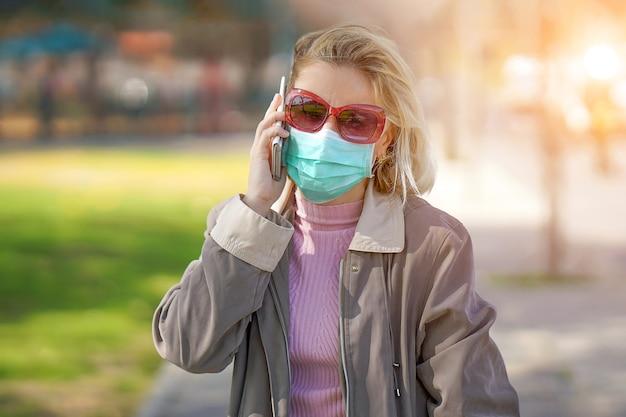 Kobieta na ulicy w masce medycznej i mówi przez telefon. atrakcyjny nieszczęśliwy model z grypą na zewnątrz. kobieta nosi maskę medyczną.