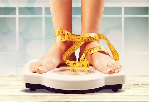 Kobieta na wadze i taśmie mierniczej
