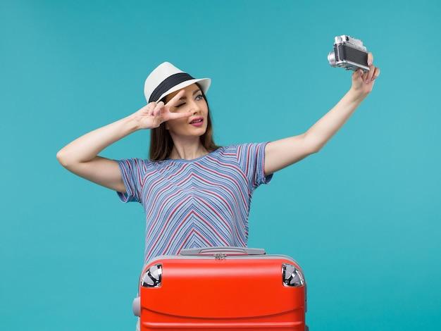 Kobieta na wakacjach trzyma aparat robiący zdjęcie na niebiesko