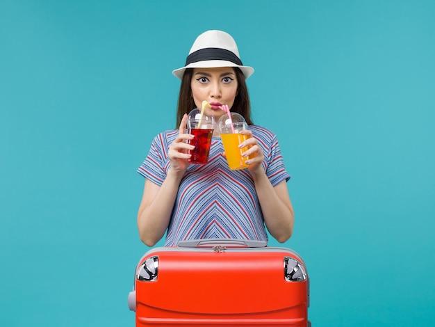 Kobieta na wakacjach trzymająca świeże napoje na niebiesko