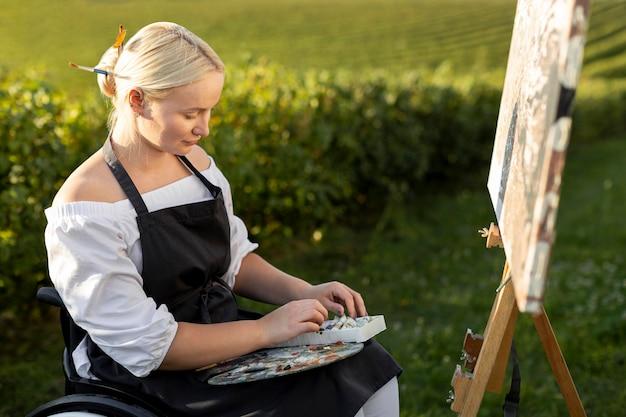 Kobieta na wózku inwalidzkim malowanie na zewnątrz w przyrodzie