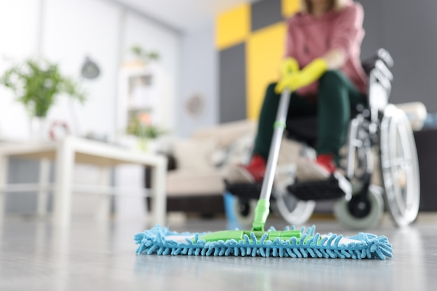 Kobieta na wózku inwalidzkim myje podłogę mopem. koncepcja sprzątania i osób niepełnosprawnych