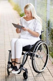 Kobieta na wózku inwalidzkim na zewnątrz z tabletem