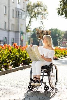 Kobieta na wózku inwalidzkim, patrząc na mapę na zewnątrz
