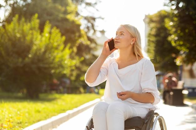 Kobieta na wózku inwalidzkim rozmawia przez telefon na zewnątrz