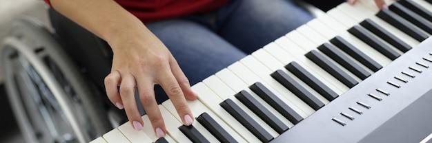 Kobieta na wózku inwalidzkim studiuje zbliżenie na fortepian