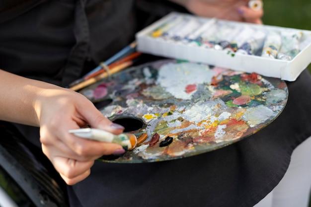 Kobieta na wózku inwalidzkim, trzymając paletę farb