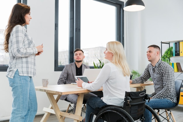 Kobieta na wózku inwalidzkim uczęszcza spotkania w biurze