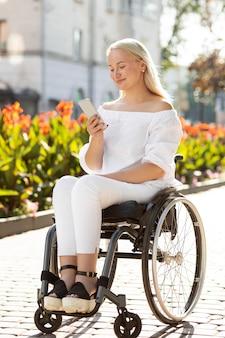Kobieta na wózku inwalidzkim w mieście przy użyciu smartfona